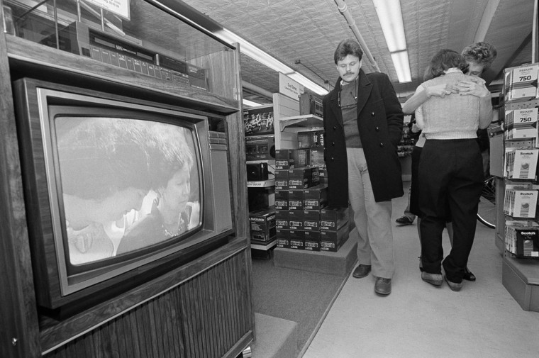 In this Friday, Feb. 1, 1986 file photo, customer David Kimball of Manchester, N.H. reacts as store employees Lynne Beck of Salisbury, N.H. and Lisa Olson, far right, of Manchester, N.H., embrace each other as they watch the Houston memorial service for the astronauts who died in the space shuttle Challenger explosion on a television in a store in Concord, N.H. Pictured on the television screen are family members of one of the astronauts. (AP Photo/Charles Krupa)