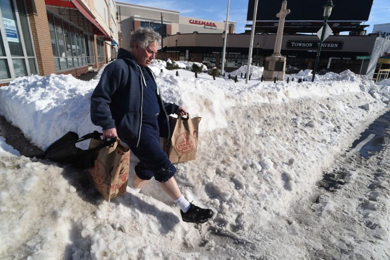 Ronn Pineo of Towson navigates a narrow opening in the snow banks near Towson Circle, after completing some food shopping. Pedestrians in many areas were forced to walk in the street due to uncleared sidewalks. (Amy Davis / Baltimore Sun)