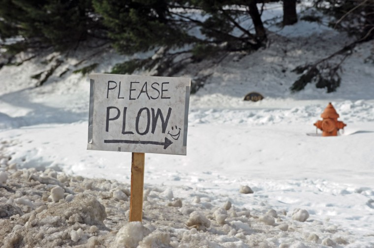 "A ""Please Plow"" sign put up by Craig Kirby, a resident on Springlake Way and Northern Parkway, pleads for a plow truck to go down his street. (Kenneth K. Lam / Baltimore Sun)"