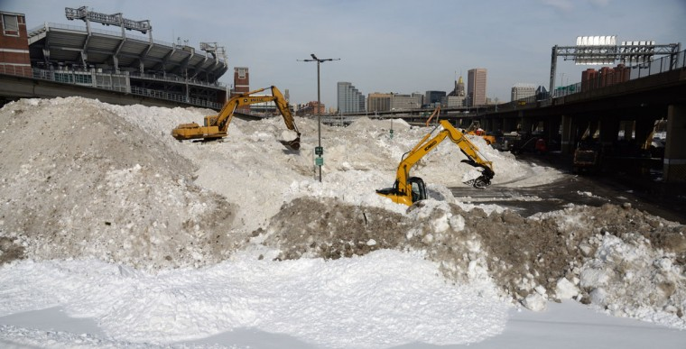 Excavators pile up snow brought in by dump trucks in a parking lot near M&T Bank Stadium. (Kim Hairston/Baltimore Sun)