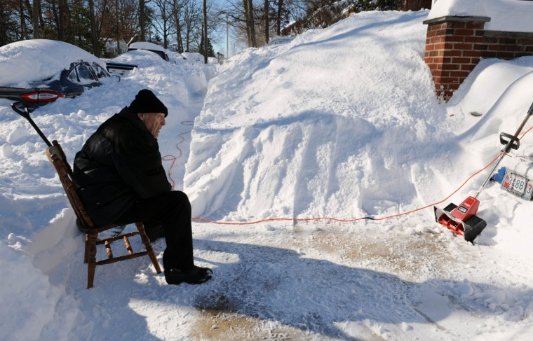 After many hours of shoveling with his power shovel, Mario Ciliotta takes a break on his clean sidewalk in the 700 block of Overbrook Road in the unplowed Anneslie neighborhood Sunday afternoon. (Karen Jackson / Baltimore Sun Media Group)