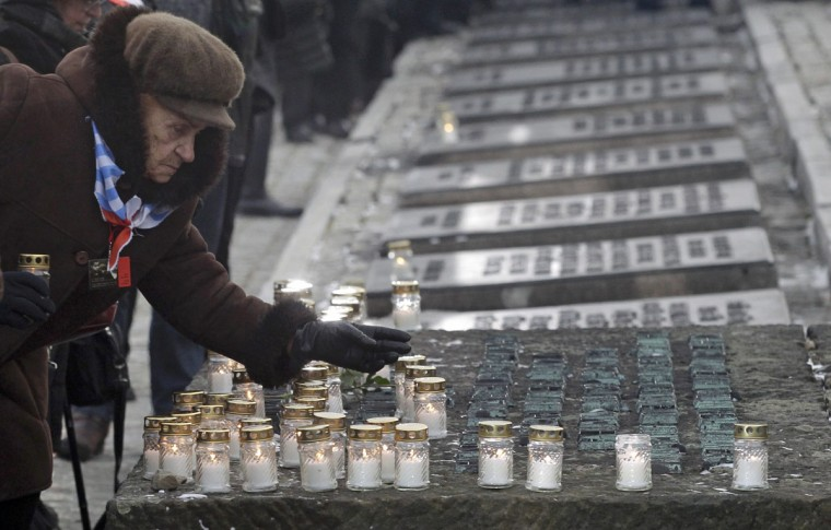 A Holocaust survivor places a lit candle at the Monument of the Victims during ceremonies to mark the 69th anniversary of the liberation and commemorate the victims of the Holocaust at the former Auschwitz-Birkenau concentration camps January 27, 2014. The world marks International Holocaust Remembrance Day on January 27 to remember those who died during the Nazi organised genocide during World War Two that cost the lives of millions of Jews, Roma and Sinti, homosexuals and opponents to Germany's fascist regime and its collaborators. (REUTERS / Kacper Pempel)