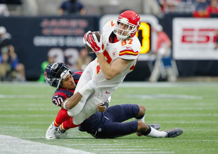 Travis Kelce #87 of the Kansas City Chiefs is tackled by Kevin Johnson #30 of the Houston Texans in the second quarter during the AFC Wild Card Playoff game at NRG Stadium on January 9, 2016 in Houston, Texas. (Thomas B. Shea/Getty Images)