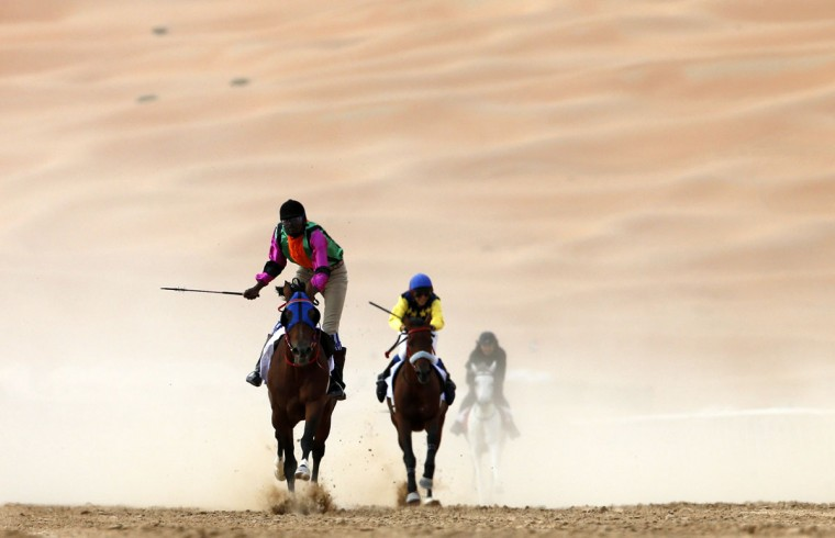Jockeys compete in a race for purebred Arab horses during the Liwa 2016 Moreeb Dune Festival on January 5, 2016, in the Liwa desert, 250 kilometers west of the Gulf emirate of Abu Dhabi. (KARIM SAHIB/AFP/Getty Images)