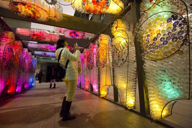 Spectators look at litre of light by British artist Mick Stephenson on show as part of the lumiere light festival in London on January 14, 2016. London hosts a festival that brings together international light artists to create installations across the capital. (JUSTIN TALLIS/AFP/Getty Images)