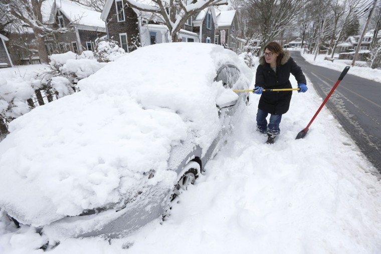 Johna McVey, of Falmouth, Mass., shovels out her car in front of her home Sunday, Jan. 24, 2016, in Falmouth. A massive winter storm buried much of the U.S. East Coast in a foot or more of snow Saturday. (AP Photo/Steven Senne)