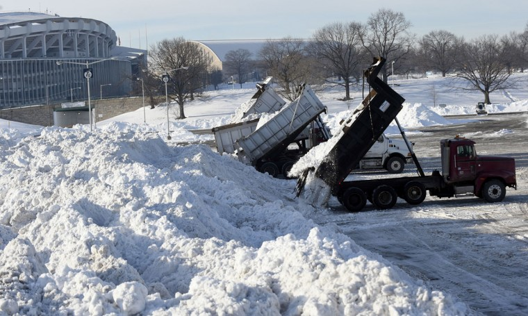 Trucks dump their loads of snow in the parking lots of RFK Stadium in Washington, Monday, Jan. 25, 2016, as the nation's capital digs out following a monster weekend snow. (AP Photo/Susan Walsh)