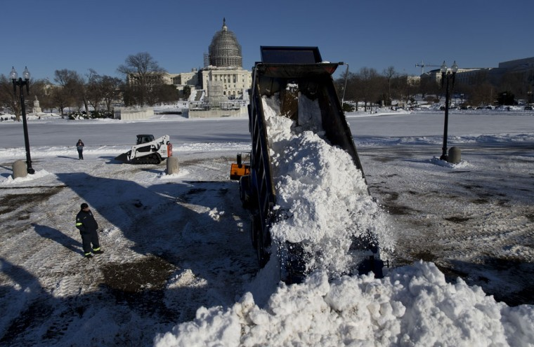 A dump truck empties a load of snow in front of the U.S. Capitol Building in Washington, Sunday, Jan. 24, 2016. Washington is digging out after a mammoth blizzard with hurricane-force winds and record-setting snowfall brought much of the East Coast to an icy standstill. (AP Photo/Carolyn Kaster)