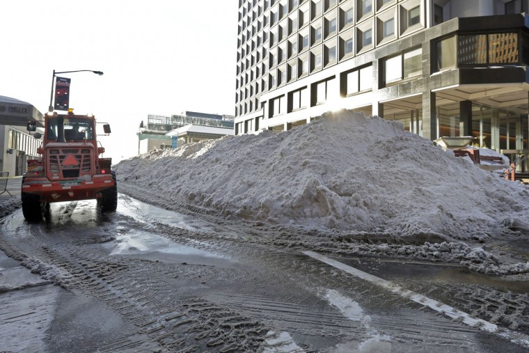 Nearly a block-long pile of plowed snow waits to be loaded into a melter, in lower Manhattan, in New York Monday, Jan. 25, 2016. East Coast residents who made the most of a paralyzing weekend blizzard face fresh challenges as the workweek begins: slippery roads, spotty transit service and mounds of snow that buried cars and blocked sidewalk entrances. (AP Photo/Richard Drew)
