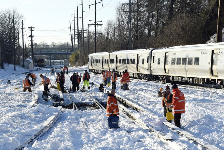 Workers clear the tracks of snow at the Port Washington branch of the Long Island Railroad, Monday, Jan. 25, 2016, in Port Washington, N.Y.. Service is suspended on the Port Washington branch due to the recent snow storm. (AP Photo/Kathy Kmonicek)