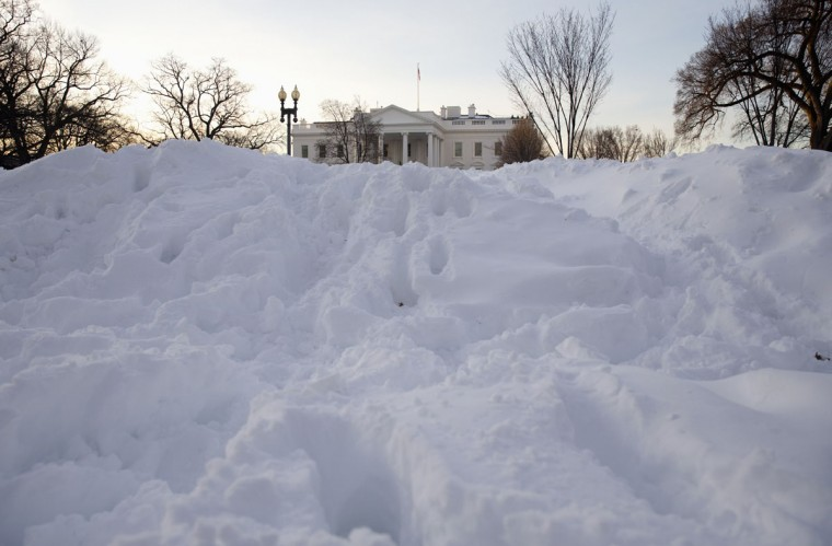 The White House peeks out from a huge pile of snow on Pennsylvania Avenue in Washington, Monday, Jan. 25, 2016. East Coast residents who made the most of a paralyzing weekend blizzard face fresh challenges as the workweek begins: slippery roads, spotty transit service mounds of snow, and closed schools and government offices.(AP Photo/Carolyn Kaster)