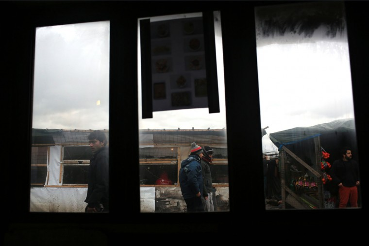 Migrants are seen through the windows of a restaurant, in the migrant camp of Calais, north of France, Thursday, Feb. 4, 2016. About 4,000 people from Syria, Sudan and other countries are estimated to be camped out in Calais as they try to reach Britain, some recently moving into new facilities but most still sleeping in what's been called Europe's biggest slum. (AP Photo/Thibault Camus)