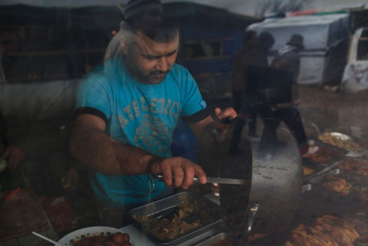 A migrant cooks in his restaurant, seen through a window, in the migrant camp of Calais, north of France, Thursday, Feb. 4, 2016. About 4,000 people from Syria, Sudan and other countries are estimated to be camped out in Calais as they try to reach Britain, some recently moving into new facilities but most still sleeping in what's been called Europe's biggest slum. (AP Photo/Thibault Camus)