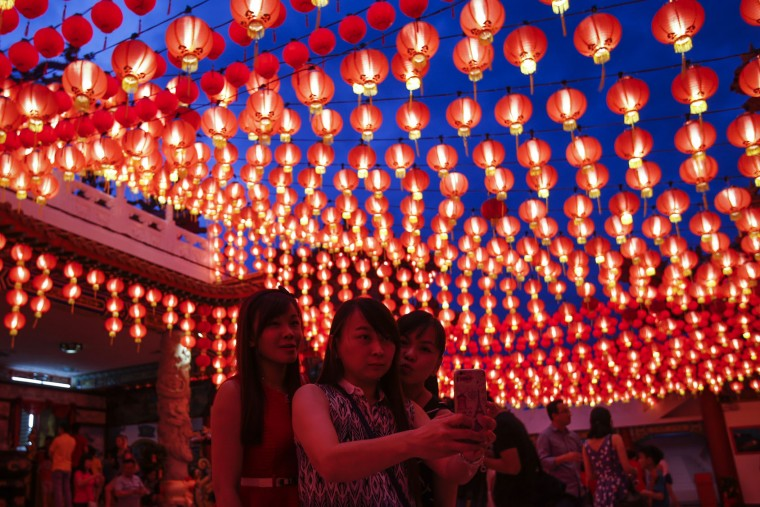 Malaysian ethnic Chinese women take a selfie under illuminated traditional Chinese lanterns on the eve of Lunar New Year in Kuala Lumpur, Malaysia, Sunday, Feb. 7, 2016. The Lunar New Year which falls on Feb. 8 this year marks the Year of the Monkey in the Chinese calendar. (AP Photo/Joshua Paul)