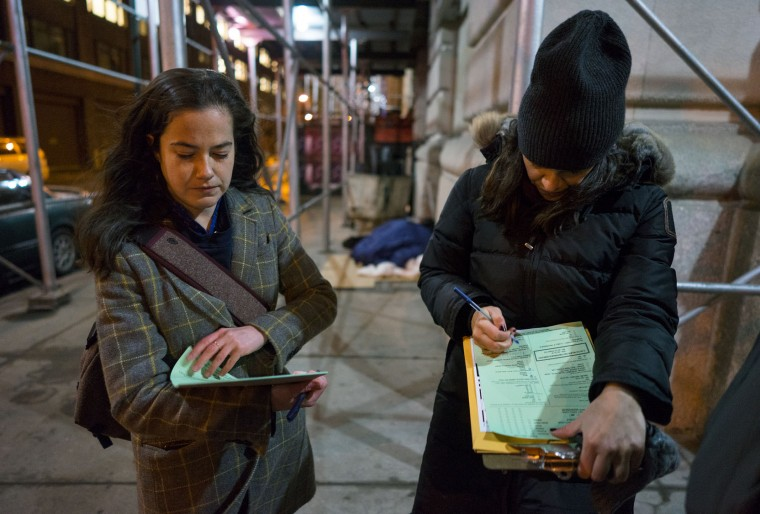After briefly speaking with homeless persons, background center, Alexis Sypek, left, and Victoria Parker, both of New York and working with The Robin Hood Foundation, an organization that helps the poor, check their notations during a count and survey of homeless persons on the streets of New York early Tuesday, Feb. 9, 2016. Hundreds of people fanned out across the city to conduct the survey just after midnight. (AP Photo/Craig Ruttle)