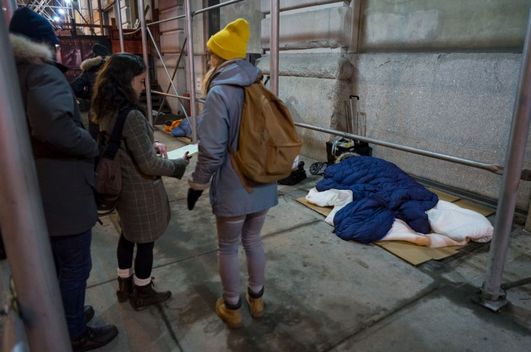 Alexis Sypek, center left, and Ashley Treni, center, both from New York and working with The Robin Hood Foundation, an organization that helps the poor, prepare their paperwork before speaking to a sleeping homeless person, right, during a count and survey of the homeless on the streets of New York early Tuesday, Feb. 9, 2016. Hundreds of people fanned out across the city to conduct the survey just after midnight. (AP Photo/Craig Ruttle)