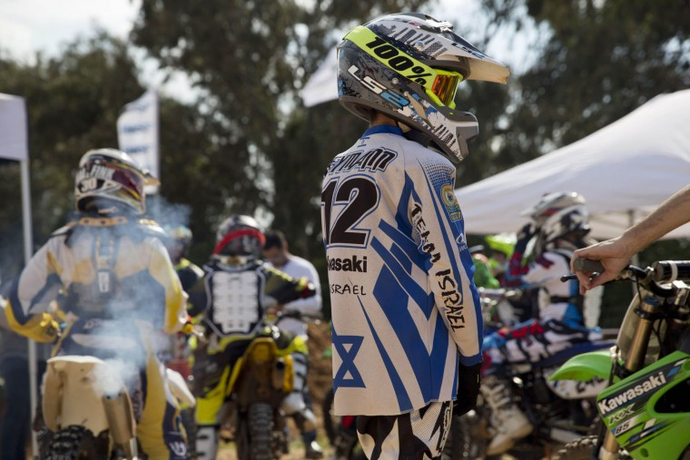 A rider listens to his coach head of a pre race for the inauguration of the first official Motocross track the MX Wingate cross country race track near Netanya, Israel, Thursday, Feb. 11, 2016. (AP Photo/Ariel Schalit)