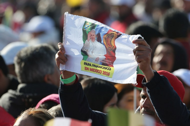 A man holds up a flag with an image of Pope Francis and the Virgin of Guadalupe as he waits for the arrival of Pope Francis at a massive open Mass in Ecatepec, Mexico, Sunday, Feb. 14, 2016. Pope Francis will give a Mass at an outdoor field in the capital's suburb of Ecatepec to an estimated crowd of 400,000 pilgrims. It is to be his biggest event during his trip to Mexico. (AP Photo/Dario Lopez-Mills)