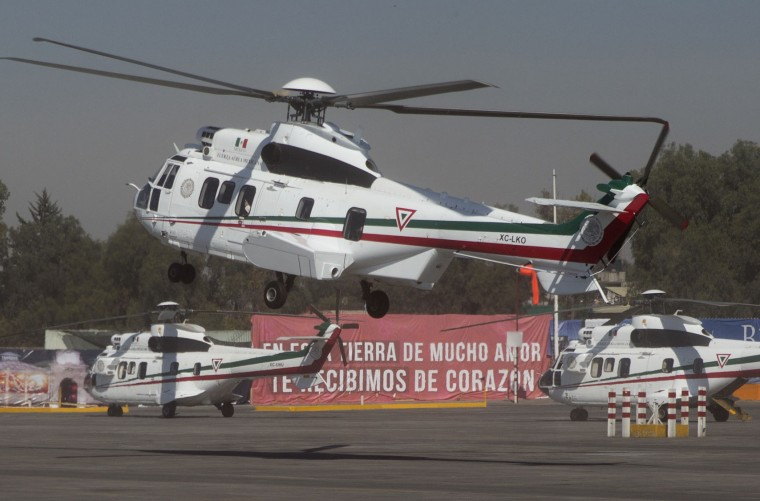 Pope Francis waves from the window of his helicopter, as he arrives in Ecatepec, Mexico state, Mexico, Sunday, Feb. 14, 2016. Pope Francis will give a Mass at an outdoor field in the capital's suburb of Ecatepec to an estimated crowd of 400,000 pilgrims. It is to be his biggest event during his trip to Mexico. (AP Photo/Rebecca Blackwell)