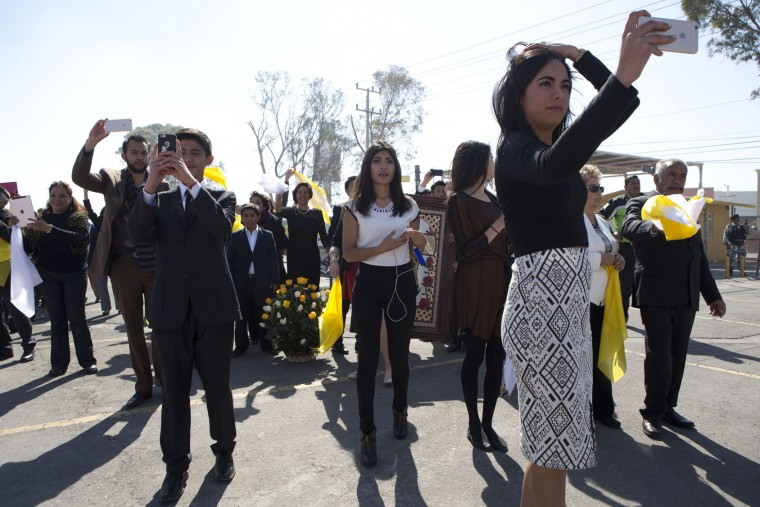 Owners of the parking lot being used as a helipad, right, along with friends and family, take pictures as the helicopter carrying Pope Francis lands, in Ecatepec, Mexico state, Mexico, Sunday, Feb. 14, 2016. Pope Francis will give a Mass at an outdoor field in the capital's suburb of Ecatepec to an estimated crowd of 400,000 pilgrims. It is to be his biggest event during his trip to Mexico. (AP Photo/Rebecca Blackwell)