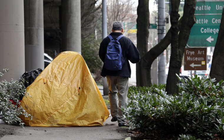 A man walks around a tent blocking a sidewalk in Seattle on Wednesday, Feb. 17, 2016. Seattle voters have agreed to tax themselves four separate times since 1986 to pay for affordable housing. The mayor recently proposed raising another $290 million with another housing levy on the November ballot. (AP Photo/Elaine Thompson)