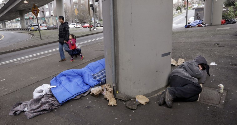 A woman walks a child past people asleep under Interstate 5 near downtown Seattle on Wednesday, Feb. 17, 2016. Even as homelessness declined slightly nationwide in 2015, it increased in urban areas, including Seattle, New York and Los Angeles. (AP Photo/Elaine Thompson)
