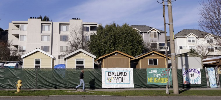 A man walks past a city-sanctioned homeless encampment of micro-homes and tents in front of apartments and condos in Seattle on Tuesday, Feb. 9, 2016. The Seattle area now ranks third in the nation in the number of housing units for the homeless. But it also has the third-highest number of homeless people. (AP Photo/Elaine Thompson)