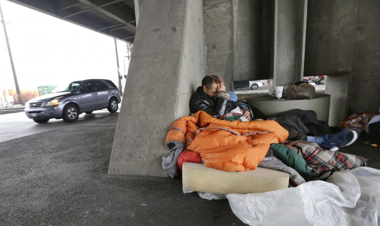 Aaron Benedict Morman wakes up in a nest of sleeping bags and a foam pad beneath a viaduct as traffic passes near him in Seattle. Morman said that he's been homeless for over 30 years, the last two in Seattle on Tuesday, Feb. 9, 2016. (AP Photo/Elaine Thompson)