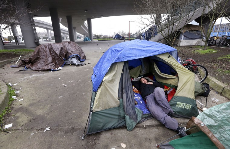 A man lies in a tent with others camped nearby, under and near an overpass in Seattle on Tuesday, Feb. 9, 2016. Seattle has the third-highest number of homeless people in the U.S. (AP Photo/Elaine Thompson)