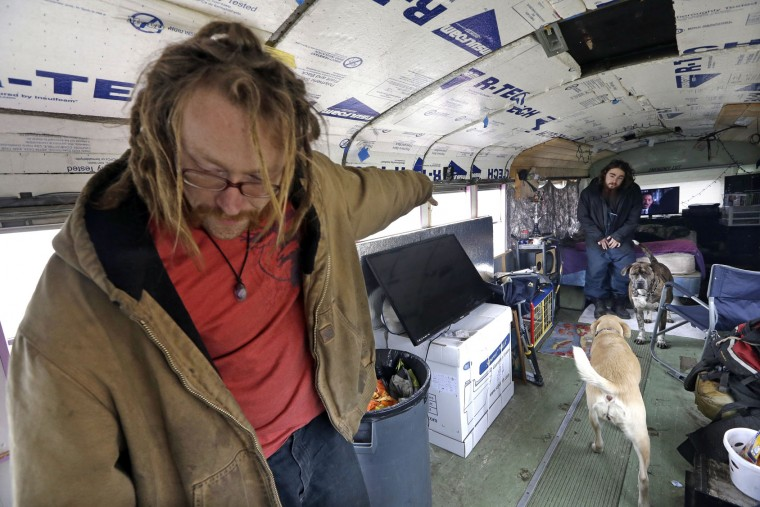 "Danny Fletcher, left, calls to his dogs as Joshua Madrid looks on in an old bus they share with three dogs in a temporary city-approved parking area for people living in their vehicles in Seattle. Fletcher, 32, who sleeps in his car at night, prefers the quiet of the parking zone to the harassment he faced in other parts of the city. ""We just want a safe place. Give us a safe place to park where neighbors won't harass us,"" he said. ""We're homeless. We're not diseased."" (AP Photo/Elaine Thompson)"