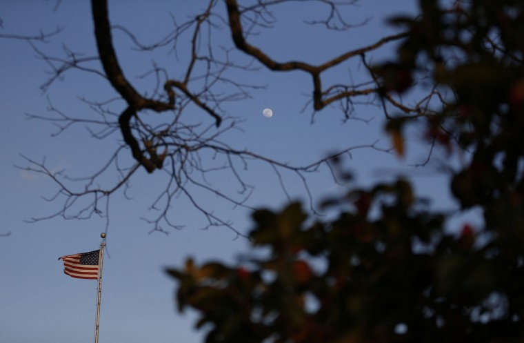 "An American flag and the moon is seen surrounded by trees in downtown in Monroeville, Ala., Friday, Feb. 19, 2016. Harper Lee, the elusive author of best-seller ""To Kill a Mockingbird,"" died Friday, Feb. 19, 2016, according to her publisher Harper Collins. She was 89. (AP Photo/Brynn Anderson)"