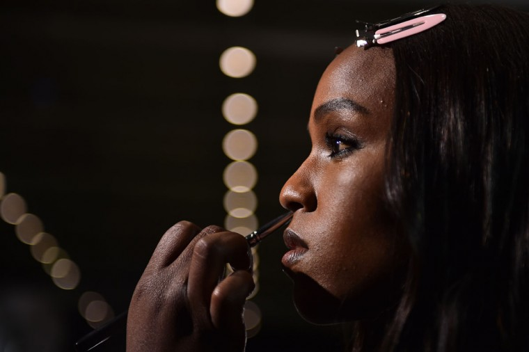 A model gets ready backstage before the show for fashion house Versace during the Women Autumn / Winter 2016 Milan Fashion Week on February 26, 2016. (AFP Photo/Gabriel Bouys)