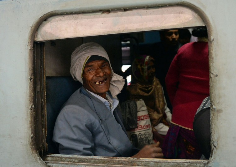 An Indian passenger smiles as he sits inside the packed general wagon of The Simanchal Express at Anand Vihar Railway Station in New Delhi on February 25, 2016. Indian Railways Minister Suresh Prabhu is set to announce the Indian Railways Budget in the country's parliament. (PRAKASH SINGH/AFP/Getty Images)