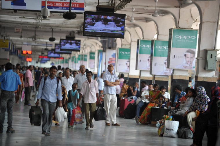 Indian passengers watch a live telecast on a platform at Secunderabad Railway Station in Hyderabad on February 25, 2016, of Indian Railways Minister Suresh Prabhu as he presents The Railway Budget at Parliament House in New Delhi. (NOAH SEELAM/AFP/Getty Images)