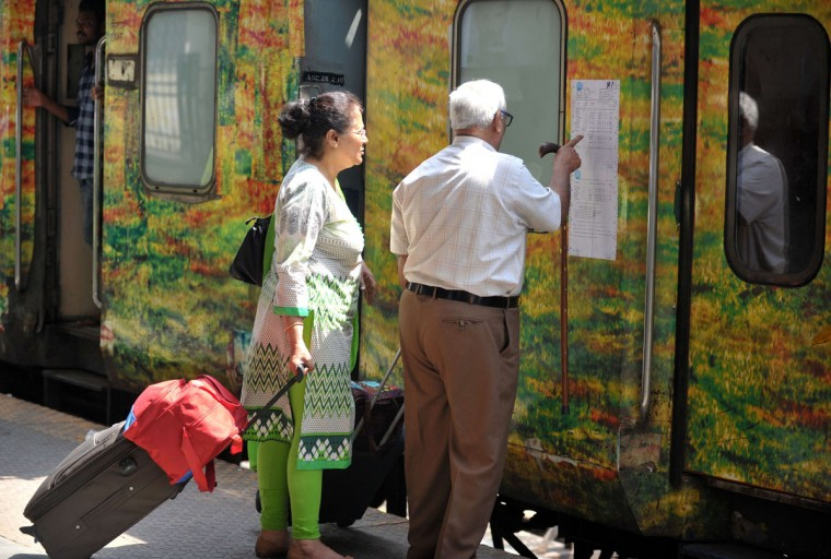 Indian passengers check the reservation chart posted on a train carriage at Secunderabad Railway Station in Hyderabad on February 25, 2016, as Indian Railways Minister Suresh Prabhu presents The Railway Budget at Parliament House in New Delhi. (NOAH SEELAM/AFP/Getty Images)