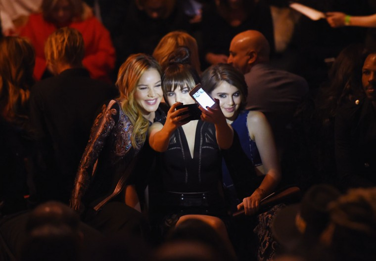 Actresses Abbie Cornish, Bailee Madison and Sami Gayle take a selfie as they attend the front row at the BCBGMAXAZRIA Fall 2016 show during New York Fashion Week at The Arc, Skylight at Moynihan Station on February 11, 2016 in New York City. (Photo by Nicholas Hunt/Getty Images)