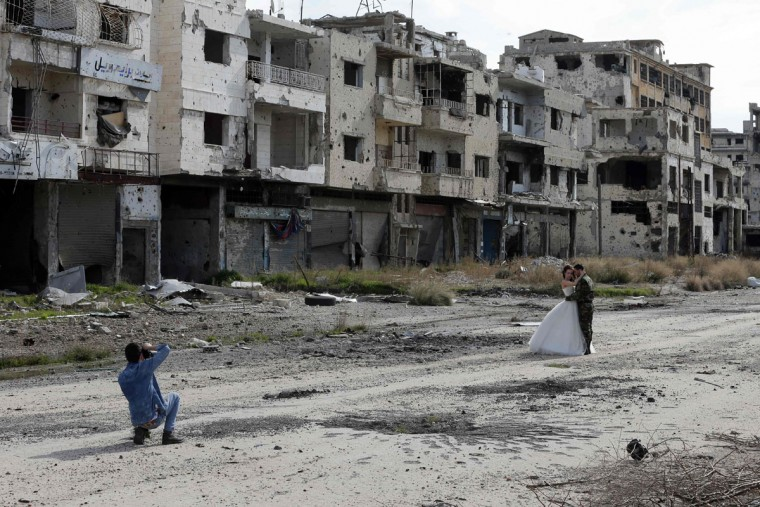 Newly-wed Syrian couple Nada Merhi, 18, and Hassan Youssef, 27, have their wedding pictures taken in the war ravaged city of Homs on February 5, 2016. A Syrian photographer thought of using the destruction of Homs to take pictures of newly wed couples to show that life is stronger than death. (Joseph Eid/AFP/Getty Images)