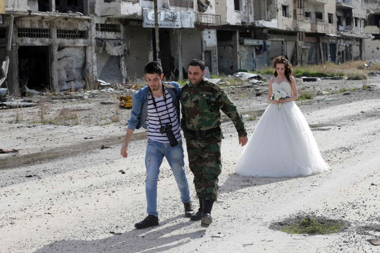 Newly-wed Syrian couple Nada Merhi, 18, and Hassan Youssef, 27, get instructions by their wedding photographer as they have their wedding pictures taken amid heavily damaged buildings in the war ravaged city of Homs on February 5, 2016. A Syrian photographer thought of using the destruction of Homs to take pictures of newly wed couples to show that life is stronger than death. (Joseph Eid/AFP/Getty Images)