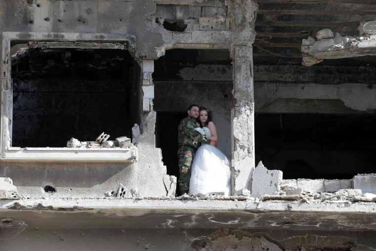 Newly-wed Syrian couple Nada Merhi,18, and Hassan Youssef, 27, pose for a wedding picture amid heavily damaged buildings in the war ravaged city of Homs on February 5, 2016. A Syrian photographer thought of using the destruction of Homs to take pictures of newly wed couples to show that life is stronger than death. (Joseph Eid/AFP/Getty Images)