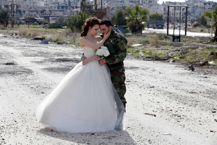 Newly-wed Syrian couple Nada Merhi, 18, and Hassan Youssef, 27, pose for a wedding picture amid heavily damaged buildings in the war ravaged city of Homs on February 5, 2016. A Syrian photographer thought of using the destruction of Homs to take pictures of newly wed couples to show that life is stronger than death. (Joseph Eid/AFP/Getty Images)