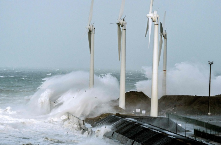 Waves break against the Boulogne-sur-mer harbor pier where wind turbines stand on February 8, 2016. (PHILIPPE HUGUEN/AFP/Getty Images)