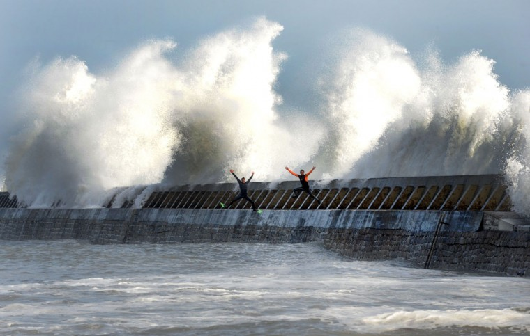 People play in front of waves on the jetty of the harbor of Lesconil, western of France on February 8, 2016. (FRED TANNEAU/AFP/Getty Images)