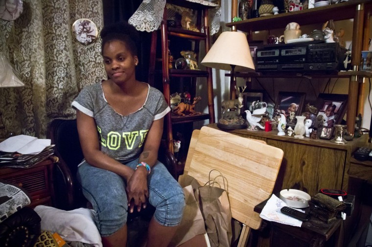In this Friday, May 22, 2015 photo, Candie Hailey, 32, sits in the small living room of her father's Bronx apartment as she talks about her incarceration at Riker's Island where most of her time was spent in solitary confinement, in New York. Hailey visits to eat and store some of her belongings at the apartment where both her younger sisters live, while staying in a nearby shelter as she struggles to regain her welfare benefits and revisit custody cases for her two sons. (AP Photo/Bebeto Matthews)