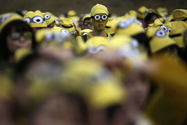 "Participants dressed as ""minions"" assemble at the start of the Minions Run charity event in Tokyo, Saturday, Feb. 13, 2016. Some 10,000 runners enjoyed one kilometer run for the charities of children. (AP Photo/Eugene Hoshiko)"