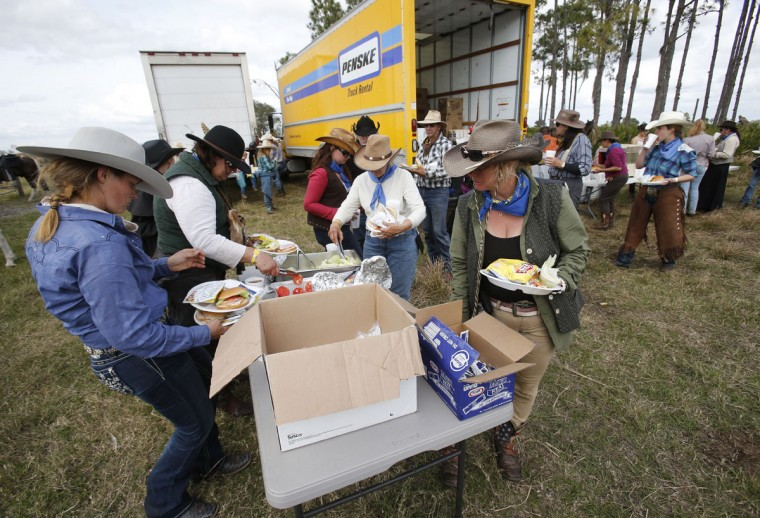In this, Tuesday, Jan. 26, 2016 photo, riders stop for lunch during the Great Florida Cattle Drive 2016, in Kenansville, Fla. Despite their efforts to re-create the life of Florida cowboys from the 19th century by wearing bonnets, suspenders and cowboy hats, and sleeping in sod fields at night, the more than 400 participants who took part in the once-in-a-decade cattle drive through the heart of Florida this week couldnít help but allow for little bits of the 21st century to seep in. Semi-trailers hauled catered food from campsite to campsite for the weeklong trek. (AP Photo/Wilfredo Lee)