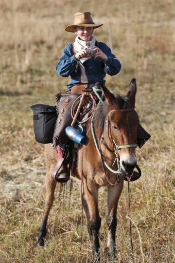 In this, Tuesday, Jan. 26, 2016 photo, a young rider takes a photo during the second day of the Great Florida Cattle Drive 2016, in Kenansville, Fla. (AP Photo/Wilfredo Lee)
