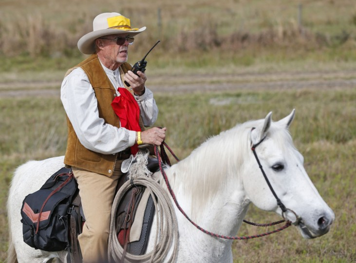 In this, Tuesday, Jan. 26, 2016 photo, Wagon Master Paul Sullivan talks on a walkie talkie as he attempts to find the best route for the wagons during the Great Florida Cattle Drive 2016, in Kenansville, Fla. The purpose of the once-a-decade Great Florida Cattle Drive was to draw attention to Floridaís deep cowboy history. Despite their efforts to re-create the life of Florida cowboys from the 19th century by wearing bonnets, suspenders and cowboy hats, and sleeping in sod fields at night, the more than 400 participants who took part in the once-in-a-decade cattle drive through the heart of Florida this week couldnít help but allow for little bits of the 21st century to seep in. (AP Photo/Wilfredo Lee)