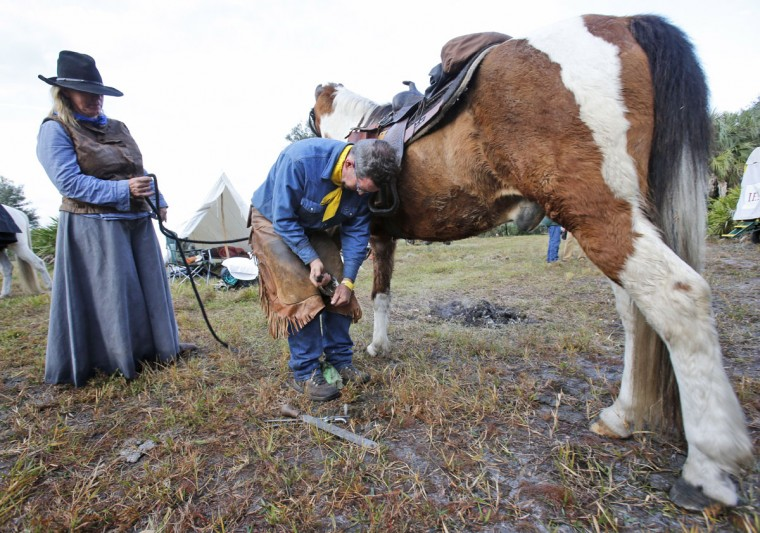 In this, Tuesday, Jan. 26, 2016 photo, Holly Huffman-Pope, left, of Polk City, Fla., watches as farrier Bryce Burnett of Zolfo Springs, Fla., works on her horse Rocky's hoof during the second day of the Great Florida Cattle Drive 2016, in Kenansville, Fla. Some things never change in cowboy life, whether in the 19th or 21st century, such as the popularity of farriers like Burnett. Every couple of miles, riders stopped him and asked for help with their horsesí feet. Rocky, had an abscess in his hoof, and Burnett cut out the infection so that it would drain. (AP Photo/Wilfredo Lee)