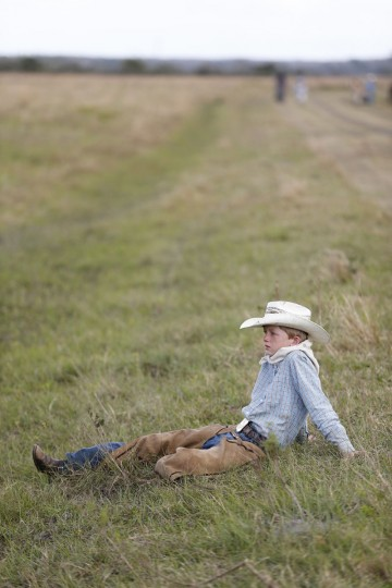 In this, Tuesday, Jan. 26, 2016 photo, Matthew Lawrence, 12, of Okeechobee, Fla., takes a break during lunch during the second day of the Great Florida Cattle Drive 2016, in Kenansville, Fla. (AP Photo/Wilfredo Lee)