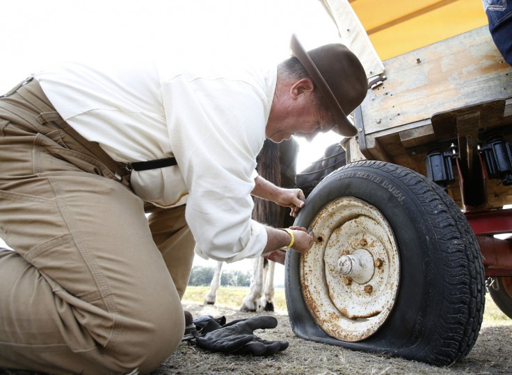In this, Tuesday, Jan. 26, 2016 photo, Malcolm Jessup of Spencer, Tenn., attempts to pull out a valve stem from a flat tire on his wagon during the Great Florida Cattle Drive 2016, in Kenansville, Fla. There was no AAA tire-repair service for the dozen or so wagons on the ride which stretched through several ranches and state land in Osceola County. The tire on Jessupís covered wagon went flat less than a mile from the campsite on the second day of the cattle drive. (AP Photo/Wilfredo Lee)